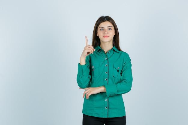Retrato de mujer joven apuntando hacia arriba en camisa verde y mirando alegre vista frontal