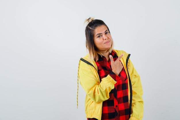 Retrato de mujer joven apuntando a la esquina superior derecha en camisa a cuadros, chaqueta y mirando alegre vista frontal