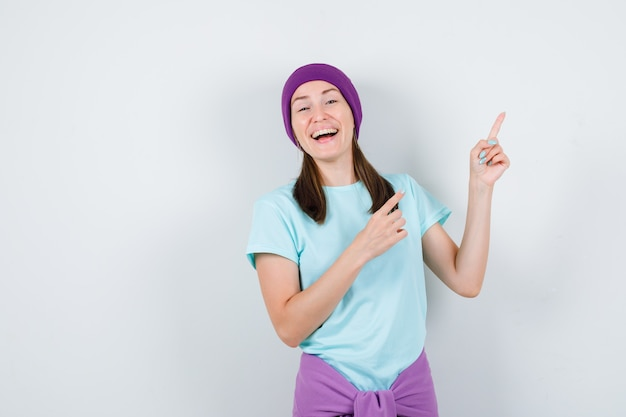 Retrato de mujer joven apuntando a la esquina superior derecha en camiseta, gorro y mirando alegre vista frontal