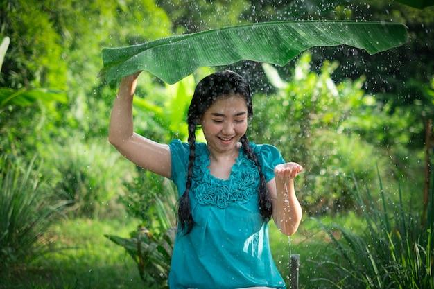Retrato de una mujer joven de asia con cabello negro sosteniendo una hoja de plátano en la lluvia en el jardín verde