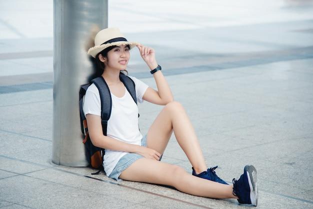 Retrato de una mujer joven asiática feliz que se sienta en la ciudad