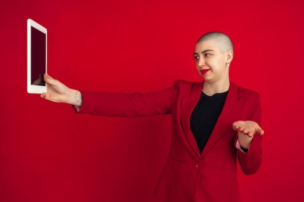 Retrato de mujer joven con aspecto extraño en la pared roja