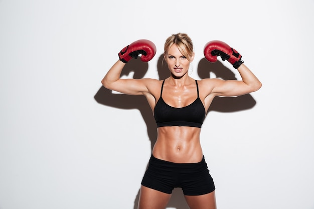 Retrato de una mujer joven atleta flexionando los músculos