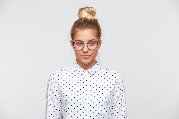 Retrato de mujer joven atractiva confiada con moño viste camisa de lunares y gafas