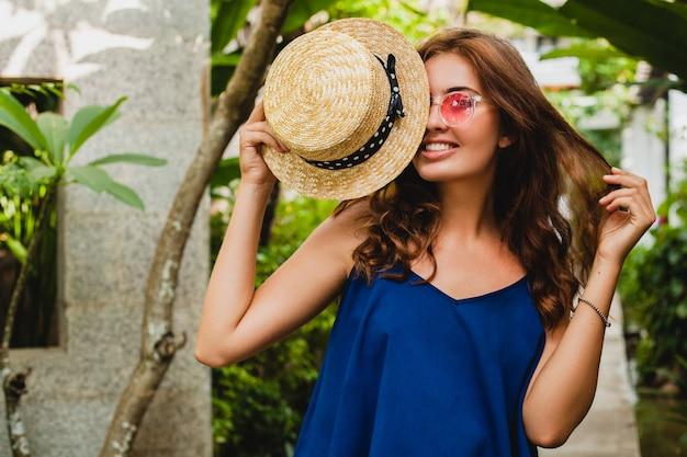 Retrato de mujer joven atractiva feliz sonriente en vestido azul y sombrero de paja vistiendo sunglassses rosa