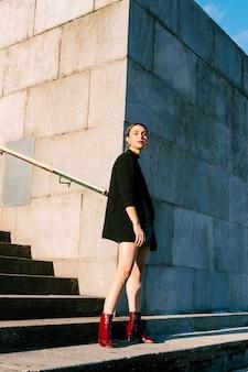 Retrato de una mujer joven atractiva que se coloca delante de la pared