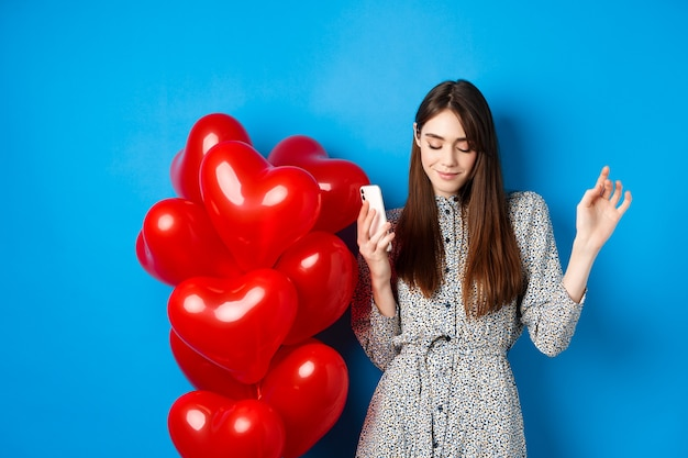 Retrato de mujer joven atractiva sosteniendo smartphone y bailando cerca de globos rojos de san valentín, de pie sobre fondo azul.