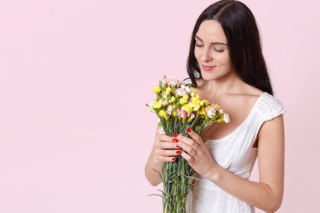 Retrato de mujer joven atractiva tierna con largo cabello negro en vestido blanco de verano con ramo, oliendo flores