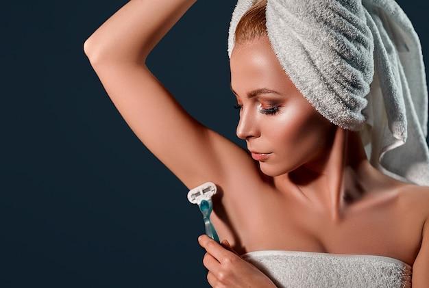 El retrato de una mujer joven y atractiva con una toalla sobre su cabeza hace que la depilación de las axilas con una navaja de afeitar en una pared negra.