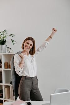 Retrato de mujer joven atractiva en traje de oficina disfruta de éxito empresarial contra el lugar de trabajo brillante.
