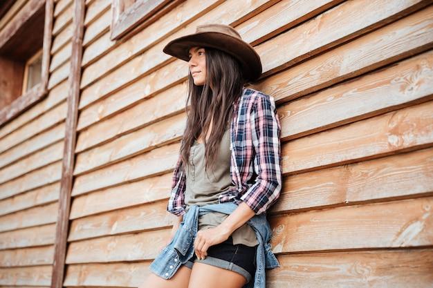 Retrato de mujer joven y atractiva vaquera con sombrero de pie cerca de la casa