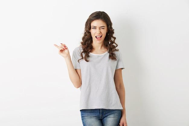 Retrato de mujer joven y atractiva vestida con camiseta casual y jeans, dedo acusador, guiñando un ojo, sonriendo, feliz, estilo hipster, aislado