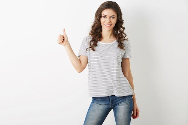 Retrato de mujer joven y atractiva vestida con camiseta casual y jeans mostrando gesto positivo, sonriente, feliz, estilo hipster, aislado, rizado, pulgar hacia arriba, delgado, hermoso, mirando a puerta cerrada