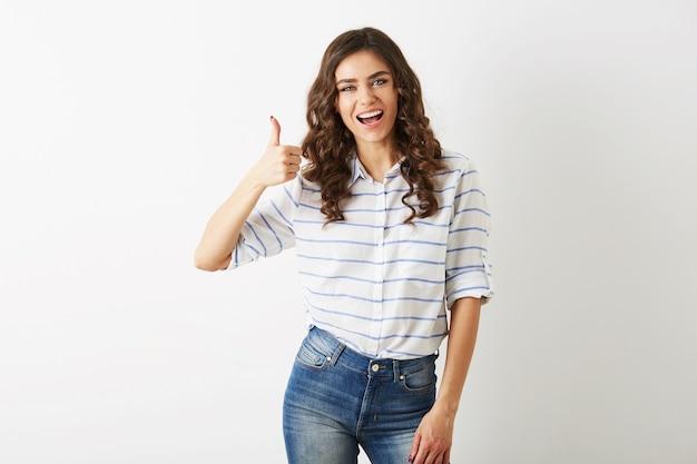 Retrato de mujer joven y atractiva vestida de casual con expresión facial emocionada, mostrando un gesto positivo, sonriente, feliz, estilo hipster, aislado, rizado, pulgar hacia arriba, delgado, hermoso, mirando a puerta cerrada
