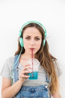 Retrato de mujer joven con auriculares beber jugo con paja