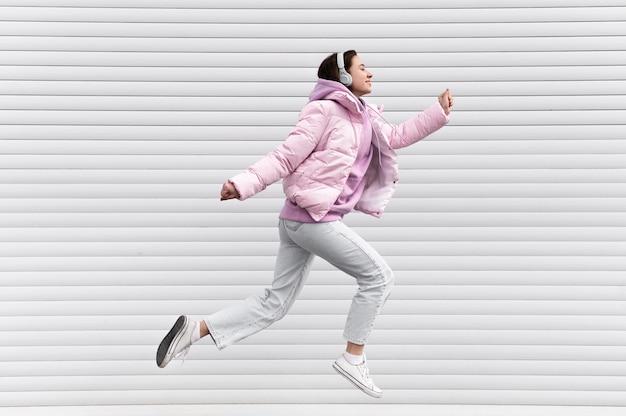 Retrato, mujer joven, con, auriculares, saltar