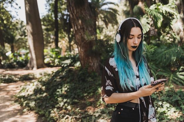 Retrato de mujer joven con auriculares en su teléfono celular de navegación principal