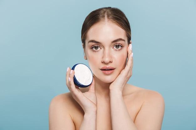 Retrato de una mujer joven bastante sorprendente posando aislada sobre pared azul cuida su piel con crema.