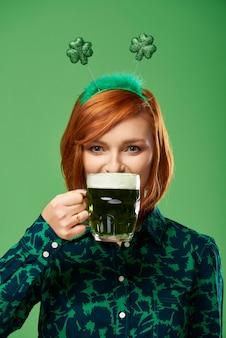 Retrato de mujer joven bebiendo cerveza