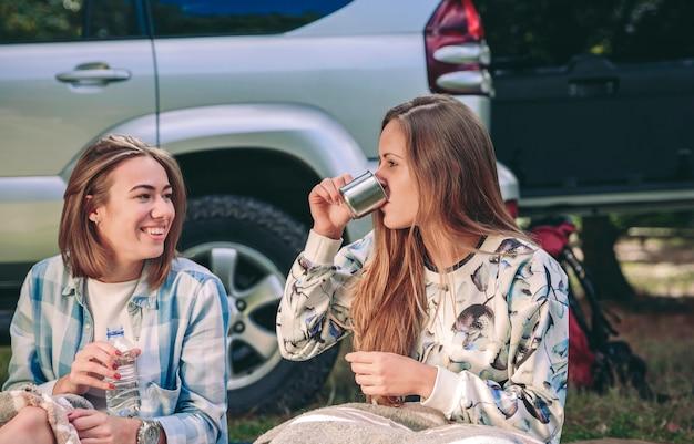 Retrato de mujer joven bebiendo una taza de café con su amiga sentada bajo una manta en el camping