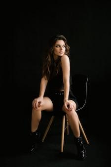 Retrato de una mujer joven y bella chica sexy en un estudio sobre un fondo negro