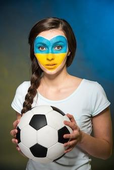Retrato de una mujer joven con una bola en sus manos.