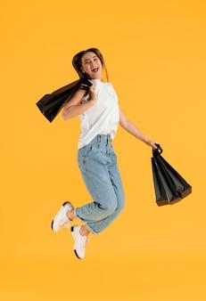 Retrato, mujer joven, con, bolsas de compras, saltar