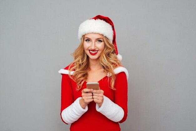 Retrato de mujer joven y bonita alegre en traje de santa mediante teléfono móvil sobre superficie gris