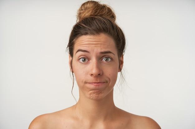 Retrato de mujer joven y bonita con ceja levantada y labios torcidos, con peinado de moño alto y sin maquillaje, decepcionado