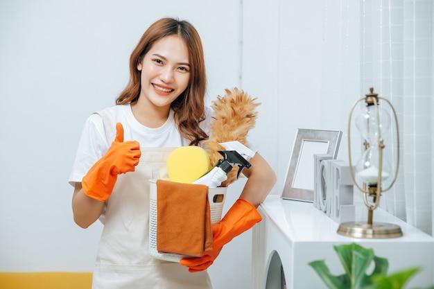 Retrato de mujer joven y bonita en delantal y guantes de goma sosteniendo una canasta de equipo de limpieza en la mano, sonríe y golpea, mirando a la cámara, espacio de copia