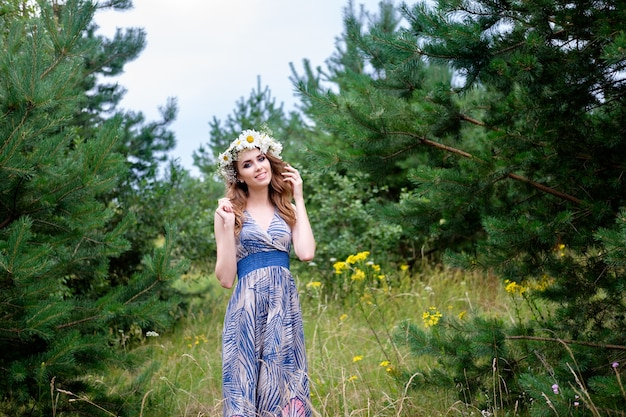 Retrato de mujer joven bonita con diadema de flores de manzanilla en la cabeza, al aire libre, maquillaje y peinado