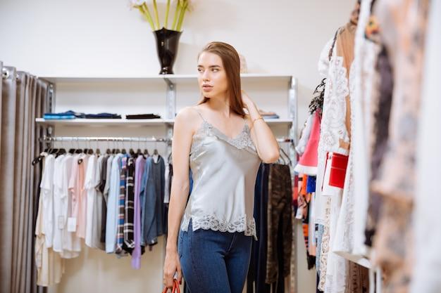 Retrato de mujer joven y bonita haciendo compras en la tienda de ropa