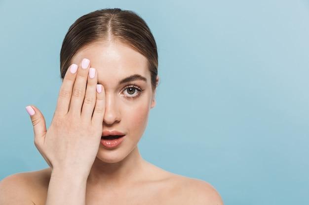 Retrato de una mujer joven y bonita posando aislada sobre una pared azul que cubre la mitad de la cara.