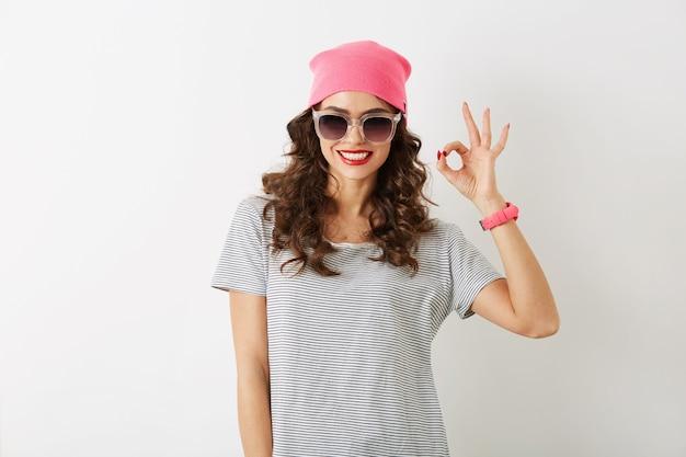 Retrato de mujer joven y bonita que muestra bien firmar, con sombrero rosa, gafas de sol, sonriendo, aislado