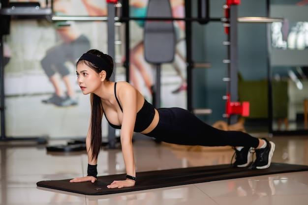 Retrato de mujer joven y bonita en ropa deportiva entrenamiento de entrenamiento físico estiramiento push up ejercicio en el piso en el moderno gimnasio, sonrisa,