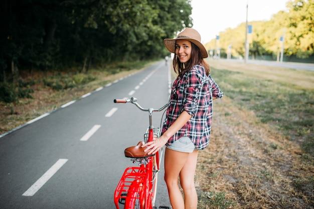 Retrato de mujer joven bonita con sombrero con bicicleta vintage roja, parque de verano verde. ciclismo al aire libre. chica en ciclo retro