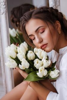 Retrato de mujer joven y bonita en vestido blanco mirando su reflejo en el espejo y sosteniendo flores de primavera. hermosa chica natural posando contra el espejo con ramo de tulipanes. dia de la mujer