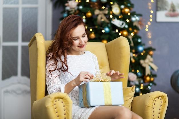 Retrato de mujer joven con cajas de regalo de navidad delante del árbol de navidad