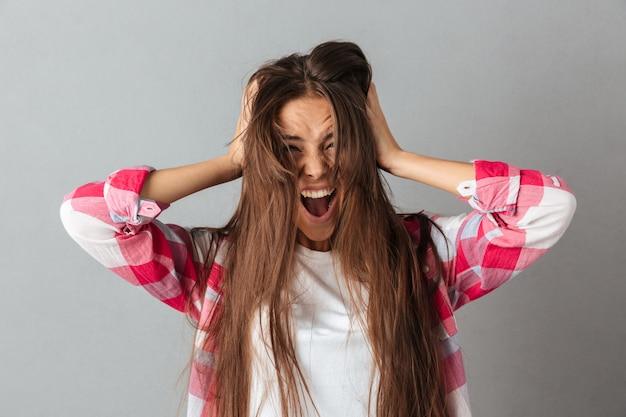 Retrato de una mujer joven en camisa a cuadros gritando