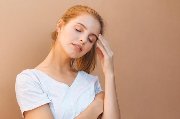 Retrato de una mujer joven cansada contra fondo marrón