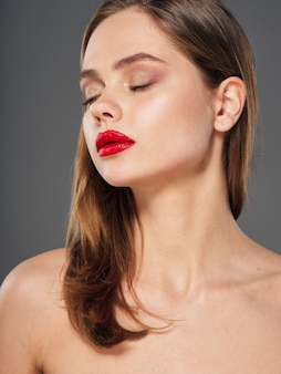 Retrato de una mujer joven con una cara bonita y lápiz labial rojo