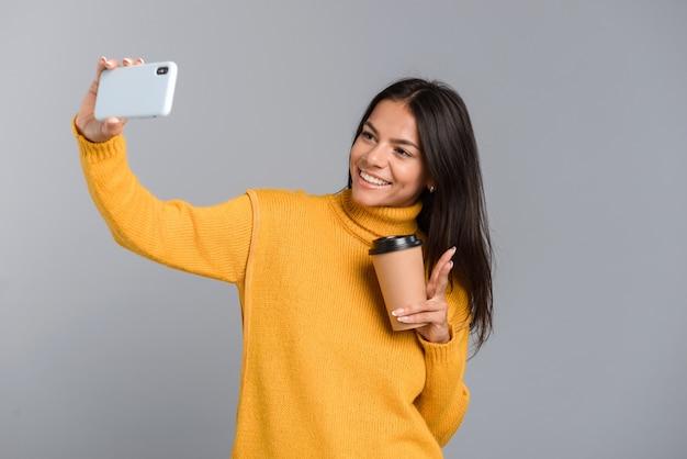 Retrato de una mujer joven casual feliz aislada sobre pared gris, sosteniendo café para llevar, tomando un selfie con teléfono móvil