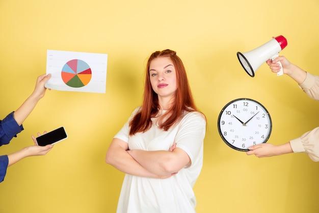 Retrato de mujer joven caucásica sobre fondo amarillo, demasiadas tareas