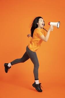 Retrato de mujer joven caucásica sobre fondo naranja de estudio.