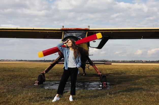 Retrato de mujer joven cerca del avión retro. campo con avión volando sobre él.
