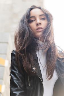 Retrato de una mujer joven en chaqueta de cuero negro mirando a cámara