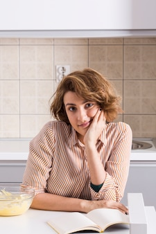 Retrato de una mujer joven en la cocina mirando a la cámara