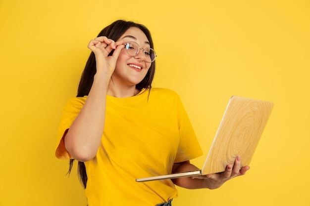 Retrato, de, mujer joven, con, computador portatil, aislado, en, pared amarilla