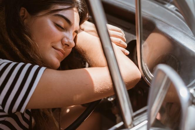 Retrato mujer joven conductor relajante disfrutar de rayo de sol