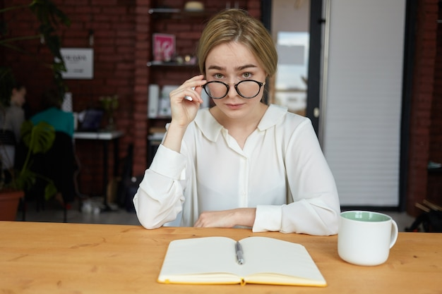Retrato de mujer joven confiada con ropa formal y gafas redondas sentado en el café con cuaderno en blanco y taza en la mesa, mirando con escrutinio expresión facial curiosa